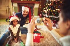 Macierzysty bierze obrazek uśmiechnięty ojciec i córka w Santa brzęczeniach obrazy stock