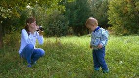 Macierzysty brać obrazki używać retro ekranową kamerę jej chłopiec w lato parku zbiory wideo