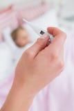 Macierzysty brać temperaturę chora córka Zdjęcia Stock