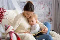 Macierzysty breastfeeding jej berbecia syna obsiadanie w wygodnym karle, wintertime zdjęcie stock