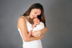 Macierzysty całowania i przytulenia nowonarodzony syn przy szarym tłem, tende Obraz Royalty Free