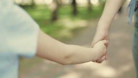 Macierzysty chwyt ręka małe dziecko córka podczas odprowadzenia w parku zbiory