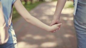 Macierzysty chwyt ręka małe dziecko córka podczas odprowadzenia w parku zdjęcie wideo