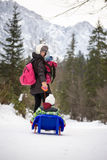 Macierzysty ciągnięcie dziecko przez śniegu na toboganie Fotografia Stock