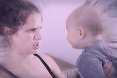 Macierzysty cierpienie od postpartum depresji trząść i krzyczy przy jej dzieckiem Fotografia Stock