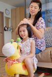 Macierzysty czesanie jej córki ` s włosy zdjęcia stock