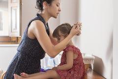 Macierzysty czesanie włosy jej córka Fotografia Royalty Free