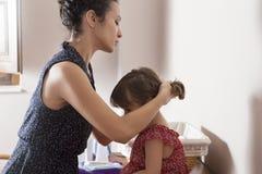 Macierzysty czesanie włosy jej córka Fotografia Stock