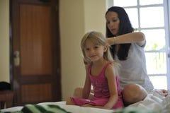 Macierzysty czesanie włosy jej córka Zdjęcie Royalty Free