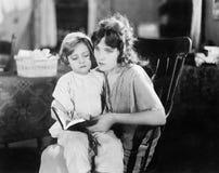 Macierzysty czytanie jej córka (Wszystkie persons przedstawiający no są długiego utrzymania i żadny nieruchomość istnieje Dostawc obraz stock
