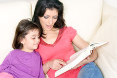 Macierzysty czytanie książki dziecko na kanapie troszkę Zdjęcie Royalty Free