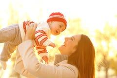 Macierzysty dźwiganie przy zmierzchem w zimie jej dziecko zdjęcia royalty free