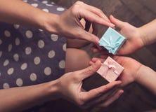 Macierzysty dawać dwa małym prezentów pudełkom jej dzieciak z otwartą ręką Zdjęcia Stock