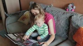 Macierzysty dopatrywanie z jej syna albumem fotograficznym zbiory wideo