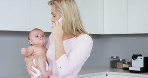 Macierzysty dzwonić podczas gdy niosący jej dziecka zbiory wideo