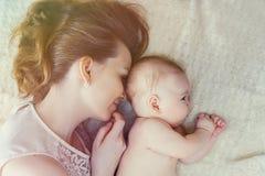 Macierzysty i dziecko jej lying on the beach w łóżku sunlight zdjęcie stock