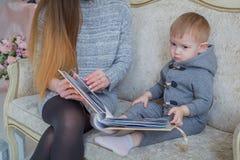 Macierzysty i dziecko jej syna przyglądający photobook fotografia royalty free
