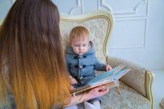 Macierzysty i dziecko jej syna przyglądający photobook obraz royalty free