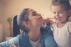 Macierzysty i jej córko bawić się z kredką wpólnie przy ho obraz stock