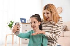 Macierzysty i jej córko używa wideo gadkę na smartphone obraz stock