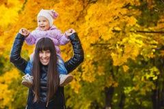 Macierzysty i jej dziecko zabawę w jesień parku Obraz Royalty Free