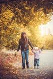 Macierzysty i jej dziecko zabawę w jesień parku Zdjęcie Royalty Free