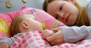 Macierzysty kładzenie jego dziecko spać na dziecka łóżku 4k zdjęcie wideo