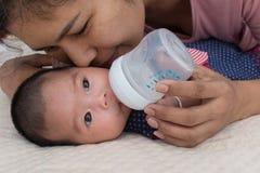 Macierzysty karmienia mleko i całuje jej dziecka fotografia royalty free