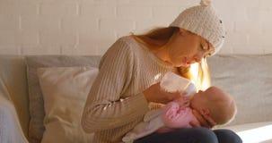 Macierzysty karmienia mleko jej chłopiec w żywym pokoju 4k zbiory