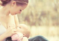 Macierzysty karmienie jej dziecko w naturze outdoors w parku Obrazy Royalty Free