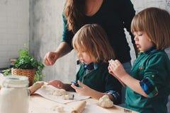 Macierzysty kucharstwo z dzieciakami w kuchni Berbeci rodzeństwa piec wpólnie i bawić się z ciastem w domu obraz royalty free
