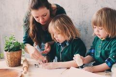 Macierzysty kucharstwo z dzieciakami w kuchni Berbeci rodzeństwa piec wpólnie i bawić się z ciastem w domu obraz stock