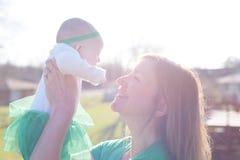 Macierzysty mienia dziecko up w jaskrawym świetle słonecznym fotografia stock