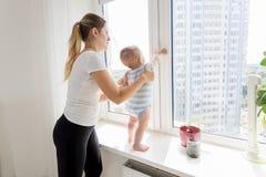 Macierzysty mienie jej dziecko podczas gdy ja stoi na windowsill i l Obraz Stock