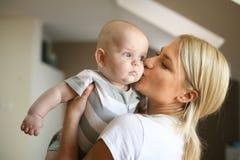 Macierzysty mienie jej mała chłopiec w rękach i całowaniu ona obrazy royalty free