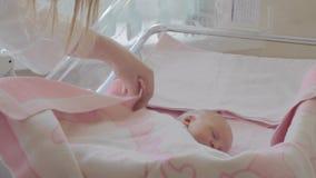 Macierzysty nakrywkowy sypialny nowonarodzony dziecko z koc w macierzyńskim szpitalu zbiory