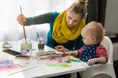 Macierzysty nauczania dziecko dlaczego malować z akwarelami zdjęcie royalty free