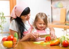 Macierzysty nauczania dziecko robi sałatki w kuchni Mamy i dzieciaka ciapania warzywo na tnącej desce z nożem _ Zdjęcie Stock