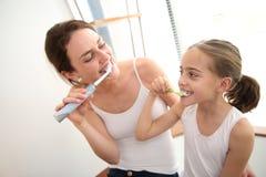 Macierzysty nauczanie jej córka dlaczego szczotkować zęby obrazy royalty free