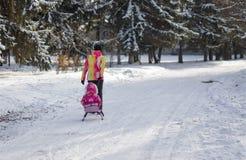 Macierzysty odprowadzenie na pustym, śnieżnym ulicznym jeżdżenie saneczki z dzieciakiem w Dnepr, Ukraina przy Grudniem, 04 2016 Obrazy Stock