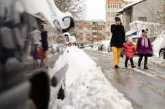 Macierzysty odprowadzenie z dwa dziećmi wzdłuż śnieżnej ulicy fotografia royalty free