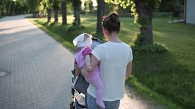Macierzysty odprowadzenie z dzieckiem w rękach, słońce błyszczy, niesie, spacerowicza zbiory wideo