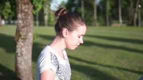 Macierzysty odprowadzenie z dziecko frachtem w zieleń parku z drzew, slowmotion i bocznego strzałem, zdjęcie wideo
