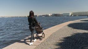 Macierzysty odprowadzenie z wózkiem spacerowym wzdłuż bulwaru miasto zbiory wideo
