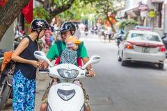 Macierzysty ojciec i dziecko w dziecko przewoźniku na hulajnodze w Hanoi, Vi fotografia royalty free