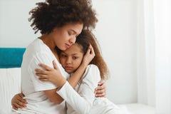 Macierzysty pocieszający jej córki, siedzi w sypialni Zdjęcie Royalty Free