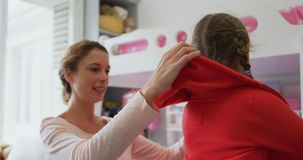 Macierzysty pomagać jej córki w być ubranym płótno w sypialni przy wygodnym domem 4k zbiory