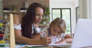 Macierzysty pomagać jej córki z pracą domową w wygodnym domu 4k zbiory wideo