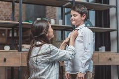 Macierzysty pomagać jej małego syna dostaje ubierający i krawat zdjęcie royalty free