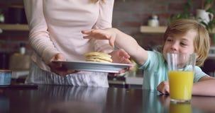 Macierzysty porcji jedzenie jej syn przy łomotać stół 4k w domu zbiory wideo